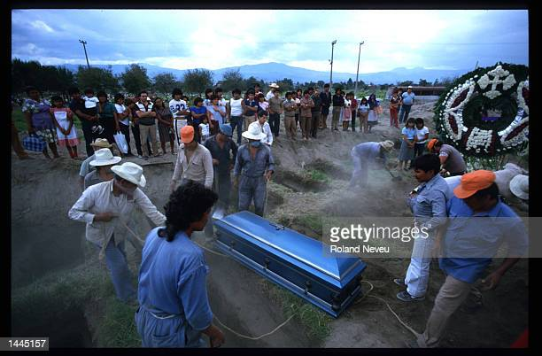 Workers prepare to lower a coffin into the ground September 22 1985 in Mexico City Mexico An earthquake registering 81 on the Richter scale hit...