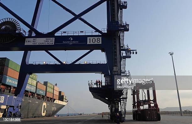 Workers prepare to unload the container ship 'Asir' at theTotal Terminal International at Algeciras port in Algeciras Spain on Friday Oct 21 2011...