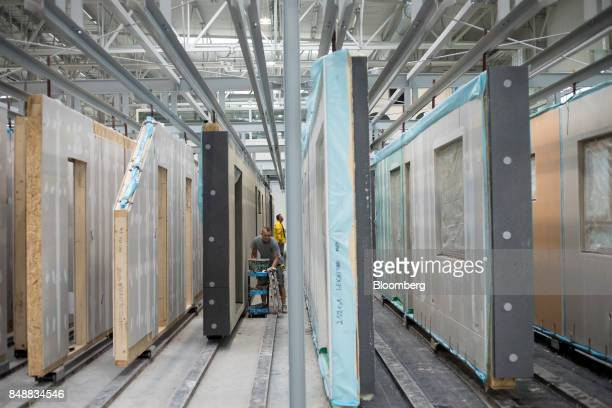 Workers prepare wall sections for prefabricated homes at the Danwood SA factory in Bielsk Podlaski Poland on Thursday Aug 23 2017 Its the end of an...