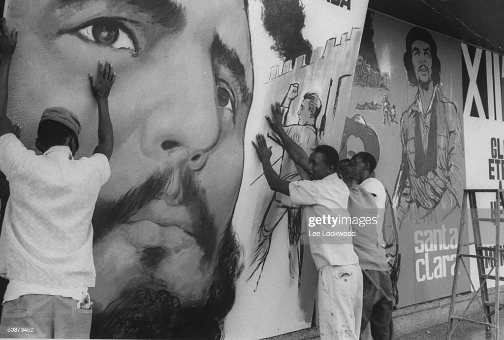 Workers preparing for celebration of 10th anniversary of Revolution erecting giant poster w. (L) Castro's face and (3L) representation of Che Guevera among other victorious depictions.