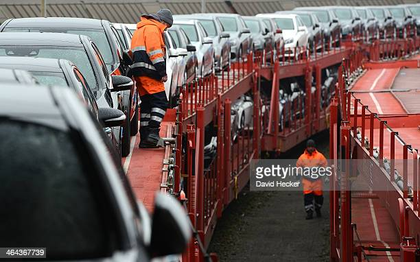 Workers preparing Mercedes cars for unloading from a freight train before they were loaded onto ships on January 22 2014 in Bremerhaven Germany...
