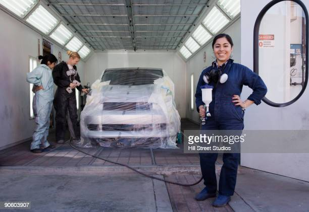 Workers preparing to paint car in auto body shop