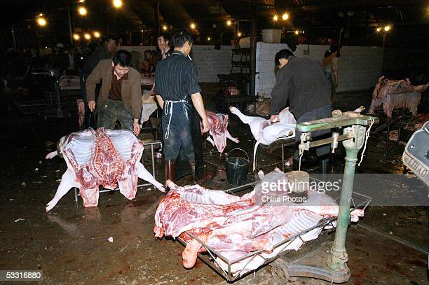 Workers process slaughtered pigs at a meat market on August 2, 2005 in Kunming of Yunnan Province, China. China has launched nationwide campaigns to...