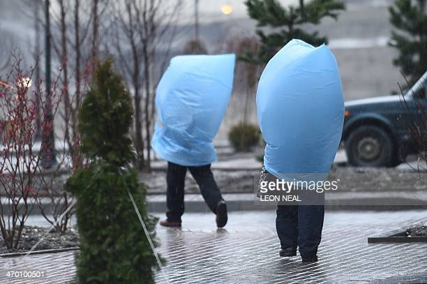 Workers protect themselves from heavy rain as they walk to the media center during the Sochi Winter Olympics on February 18, 2014. AFP PHOTO / LEON...
