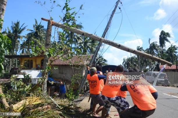Workers pull a fallen electric pylon damaged at the height of Typhoon Phanfone in Salcedo town in Eastern Samar province on December 26 2019 Typhoon...