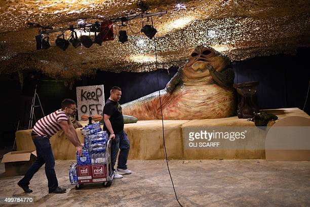 Workers push a trolley of drinks pas an animatronic model of the Star Wars character Jabba the Hutt which will feature in the unofficial Star Wars...