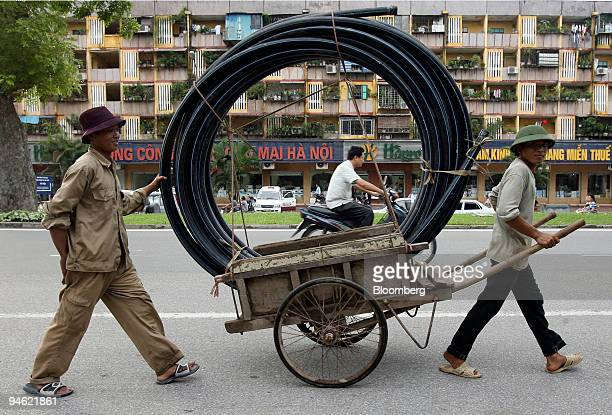 Workers push a trolly loaded with plastic piping along a street in Hanoi Vietnam on Saturday August 19 2006