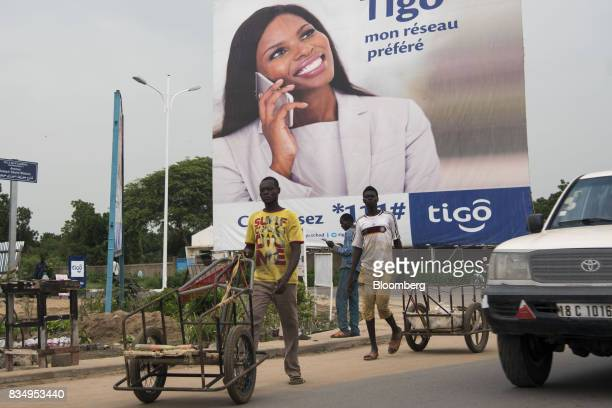 Workers push carts along a road past an advertisement for Tigo telecommunication services in N'Djamena Chad on Wednesday Aug 16 2017 African...
