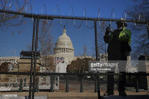 Workers put concertina razor wire along the top of the 8-foot 'non-scalable' fence that surrounds the U.S. Capitol the day after the House of...