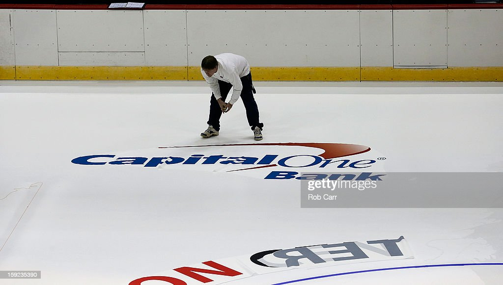 Workers put down logos on the ice for the Washington Capitals at Verizon Center on January 9, 2013 in Washington, DC.