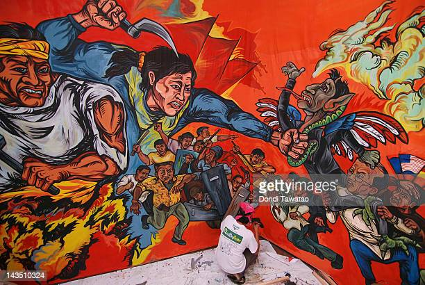Workers put finishing touches to a mural and an effigy that will be used on Labour Day by antigovernment protestors on April 28 2012 in Manila...