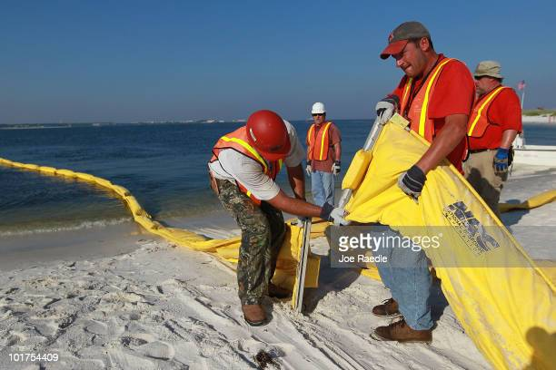 Workers put oil containment boom together to be placed on the water as they try to protect the inlet waterways from the Deepwater Horizon oil spill...