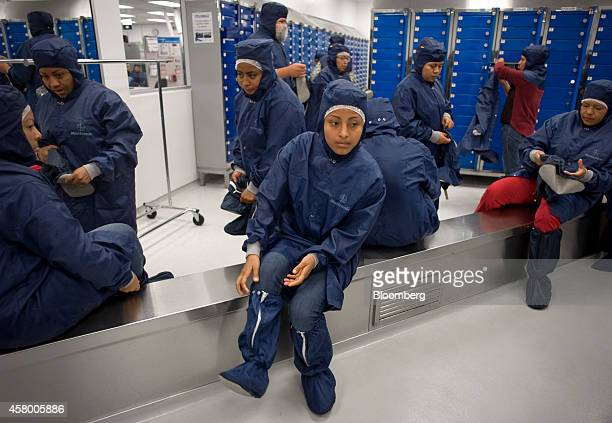 Workers put on gowns before entering a sterile environment where stent grafts and catheters are produced at the Medtronic Inc assembly plant in...