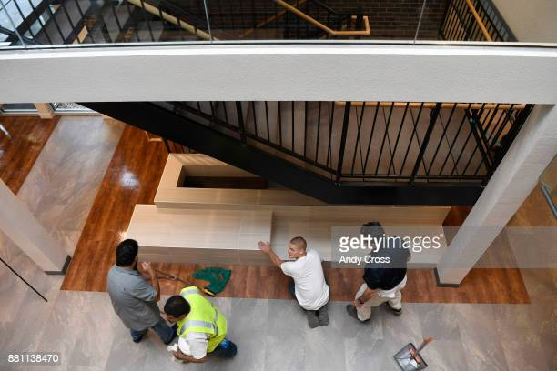Workers put on the finishing touches on the receprtion area of the openconcept Sanderson Apartments by Mental Health Center of Denver a threestory...