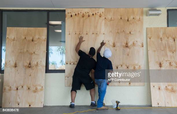 Workers put plywood over the windows at a Publix Supermarket in preparation for Hurricane Irma in Miami Florida September 7 2017 Hurricane Irma will...