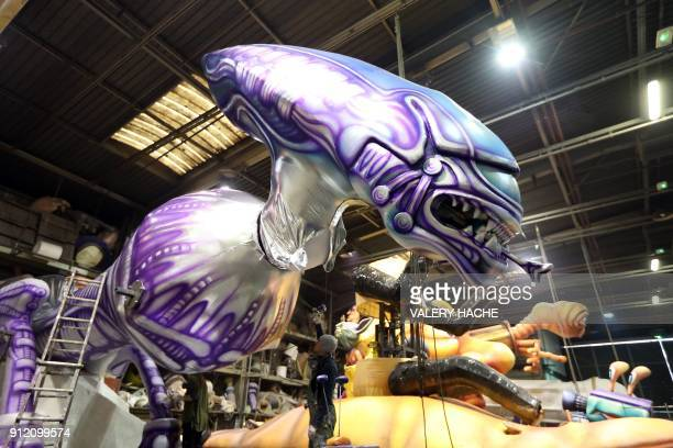 Workers put the final touch to a giant figure depicting the Alien movie monster character Xenomorph XX121 during preparations of floats for the...