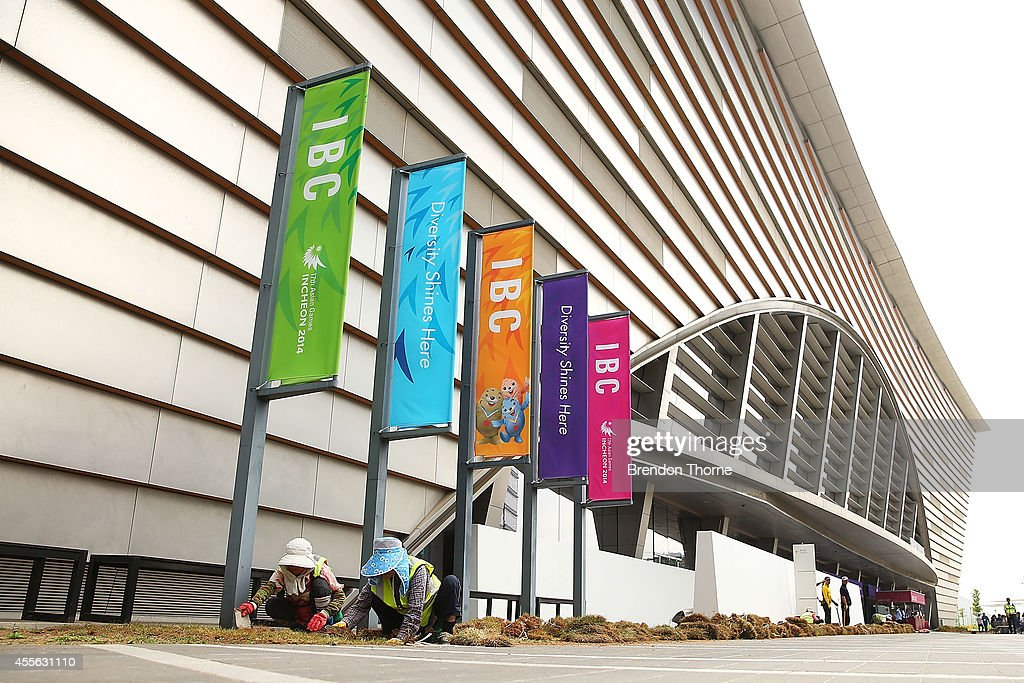 Workers put the final touches on the garden outside the International Broadcast Centre prior to the 17th Asian Games on September 18, 2014 in Incheon, South Korea.