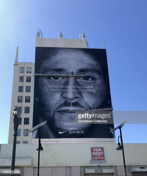 Workers put the finishing touches on a mural of Colin Kaepernick that is a Nike Advertisement that reads Believe in Something Even if it Means...
