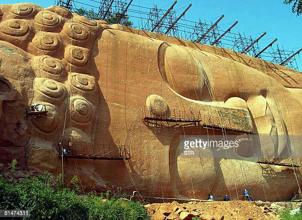 Workers put the finishing touches on the face of the world's biggest statue of a reclining Buddha on the hills of Geyang in China's eastern province...