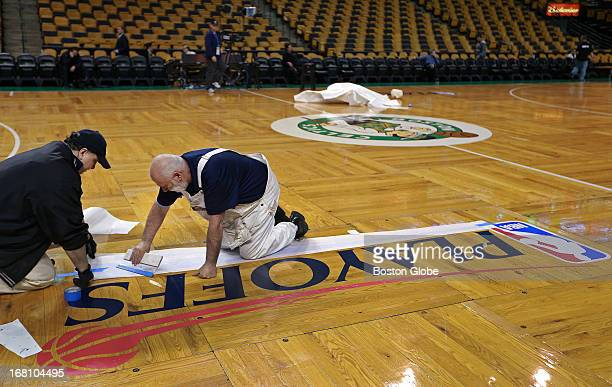 Workers put the finishing touches on the 'NBA Playoffs' stencil logo on the court before the game The Boston Celtics hosted the New York Knicks for...