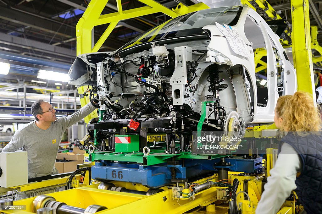 workers put together different parts on a car production line to
