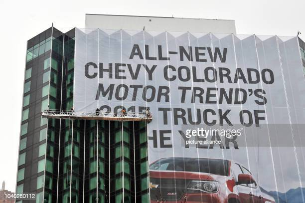 Workers put up a large banner reading 'ALLNEW CHEVY COLORADO MOTOR TRENDS`S 2015 TRUCK OF THE YEAR' during the North American International Auto Show...