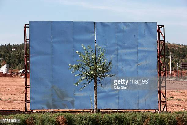 Workers put up a new sheet metal wall signaling yet another real estate development near the Kangbashi New District of Ordos City Inner Mongolia...