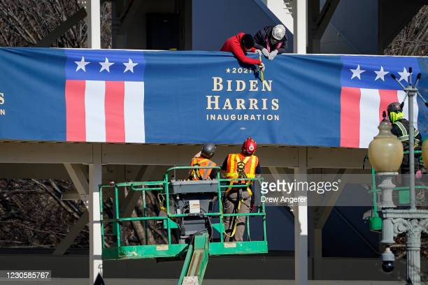 "Workers put up ""Biden-Harris"" branded bunting on a press riser along the inaugural parade route near the White House on January 14, 2021 in..."