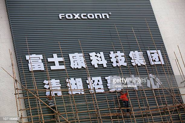 Workers put up scaffolding on a building owned by the contract manufacturer Foxconn International Holdings Ltd on November 28 2010 in Shenzhen China...