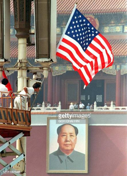 Workers put up the US and Chinese flags at Tiananmen Square in Beijing 26 June ahead of US President Bill Clinton's arrival in the Chinese capital...