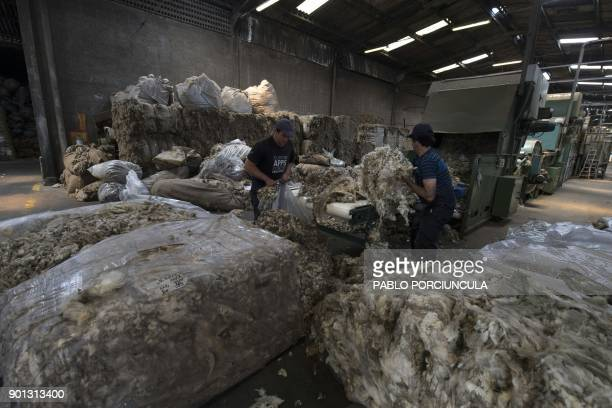 Workers put wool in a machine to be washing at Tops Fray Marcos factory in Libertad San Jose 90km west from Montevideo on December 1 2017 Located...