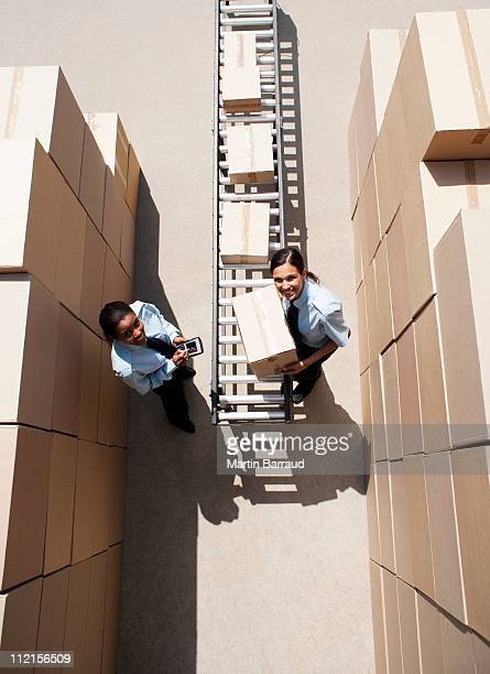 Workers putting boxes on conveyor belt