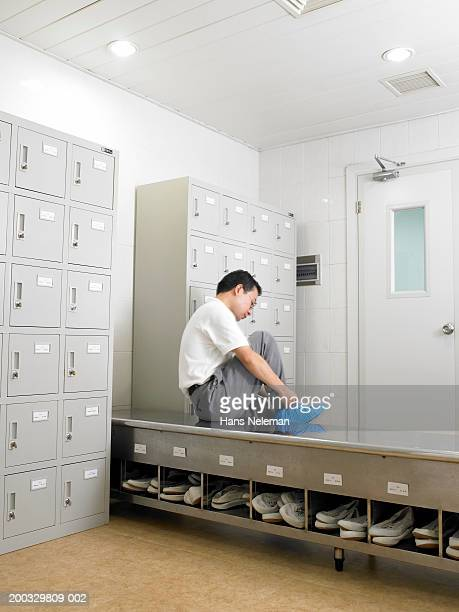 workers putting on protective foot coverings in locker room - shoe covers stock pictures, royalty-free photos & images