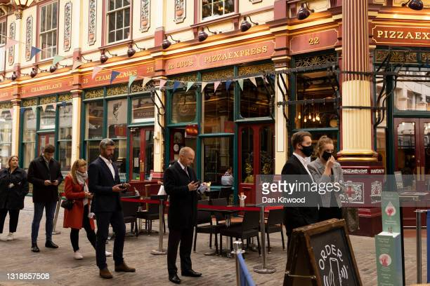 Workers queue for a restaurant in Leadenhall Market in the square mile on May 18, 2021 in London, England. Workers have begun to return to the City...