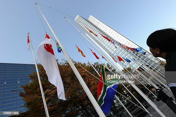 Workers raise the flags of the participating G20 countries outside the venue of the G20 Summit in Seoul on November 10 2010 World leaders on November...