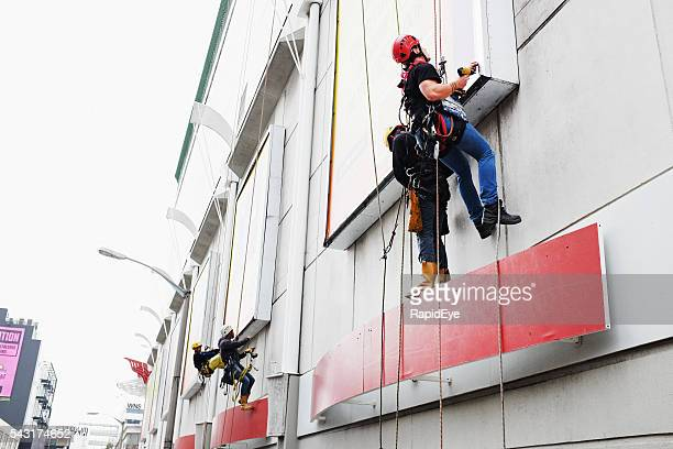 Workers rappelling down a shopping mall exterior to access billboards