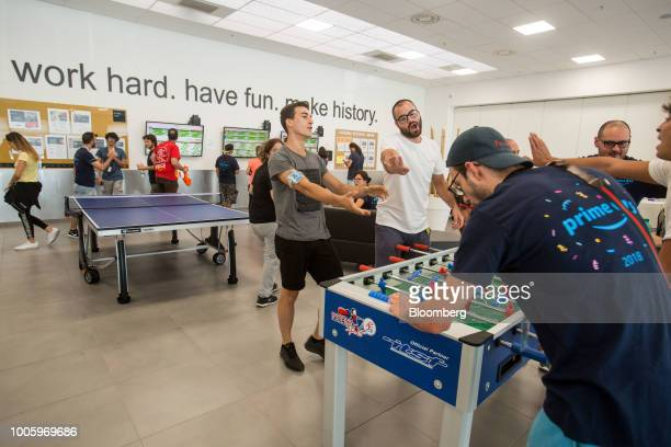 Workers react as they play table football during a lunch break at the Amazoncom Inc fulfillment center in Passo Corese Rieti Italy on Thursday July...