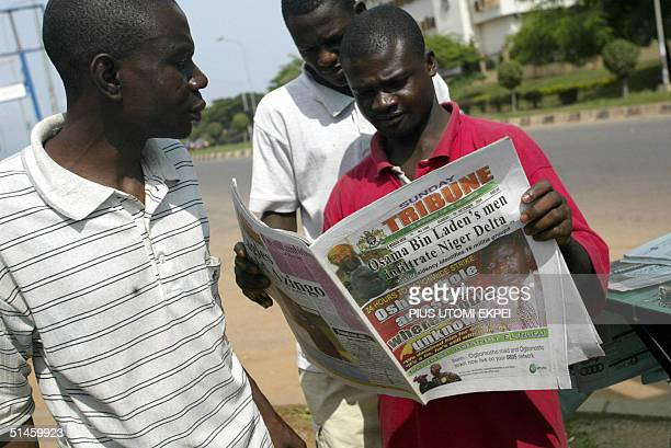 Workers read newspapers in Abuja 10 October 2004 highlighting stories about the arrest of Nigeria Labour Congress President Adams Oshiomhole and the...