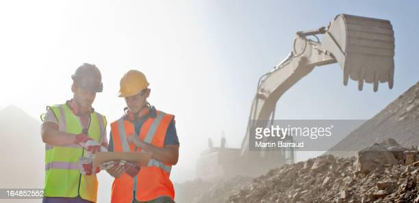 Los trabajadores lectura blueprints en quarry