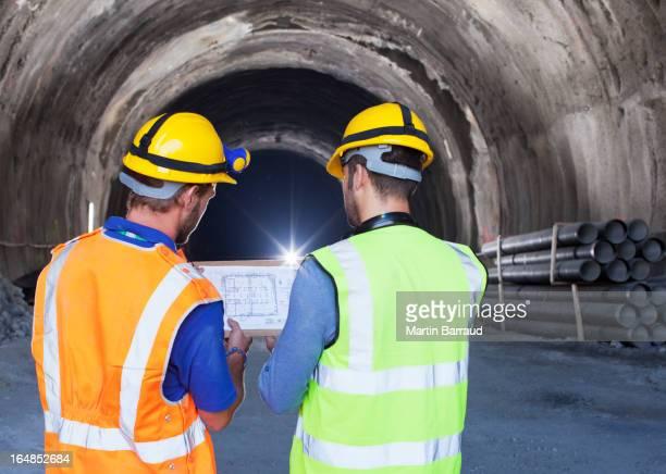 Travailleurs lecture de plan dans le tunnel