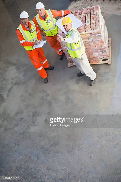 Workers reading blueprints on site