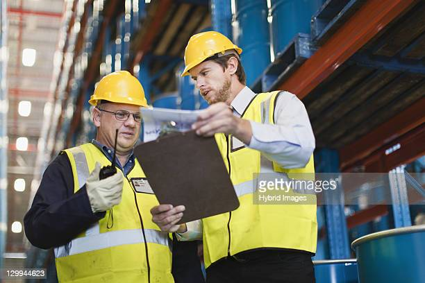 Workers reading clipboard in warehouse