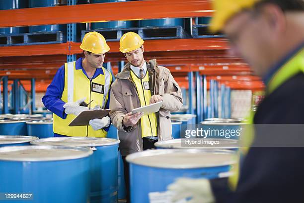 Workers reading clipboards in warehouse