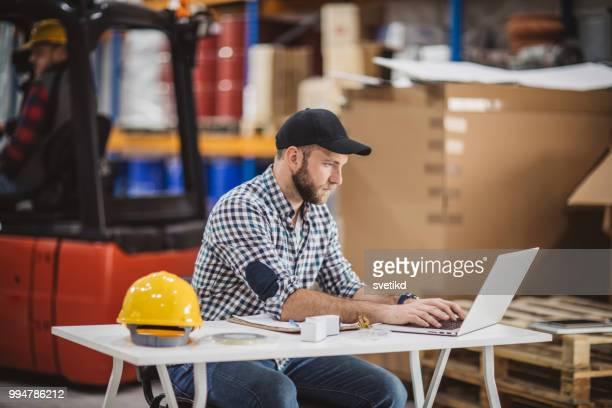 workers receiving new orders on laptop - plaid shirt stock pictures, royalty-free photos & images