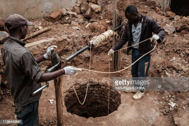 Workers recover on April 9 2019 victims' bones in a soil recovered from a pit which was used as a mass grave during the 1994 Rwandan genocide and...