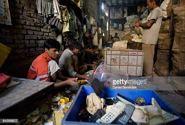 Workers recycle plastic in the Dharavi slum on February 3 2009 in Mumbai India The redevelopment of asia's largest slum the Dharavi spanning over 500...
