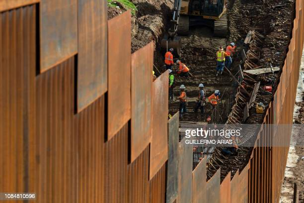 TOPSHOT Workers reinforce a section of the USMexico border fence as seen from eastern Tijuana in Baja California state Mexico on January 18 2019 A...