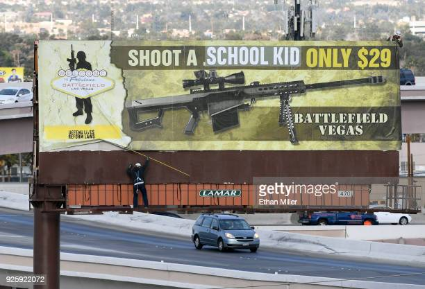 Workers remove a billboard poster for the Battlefield Vegas shooting range after it was vandalized on March 1 2018 in Las Vegas Nevada The activist...