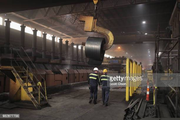 Workers remove a coil from the production line for qualitycontrol testing during steel production at the NLMK Indiana steel mill on March 15 2018 in...