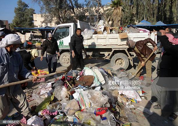 Workers remove a pile of garbage in the center of the city of Fallujah west of the capital Baghdad on January 8 following days of fighting between...